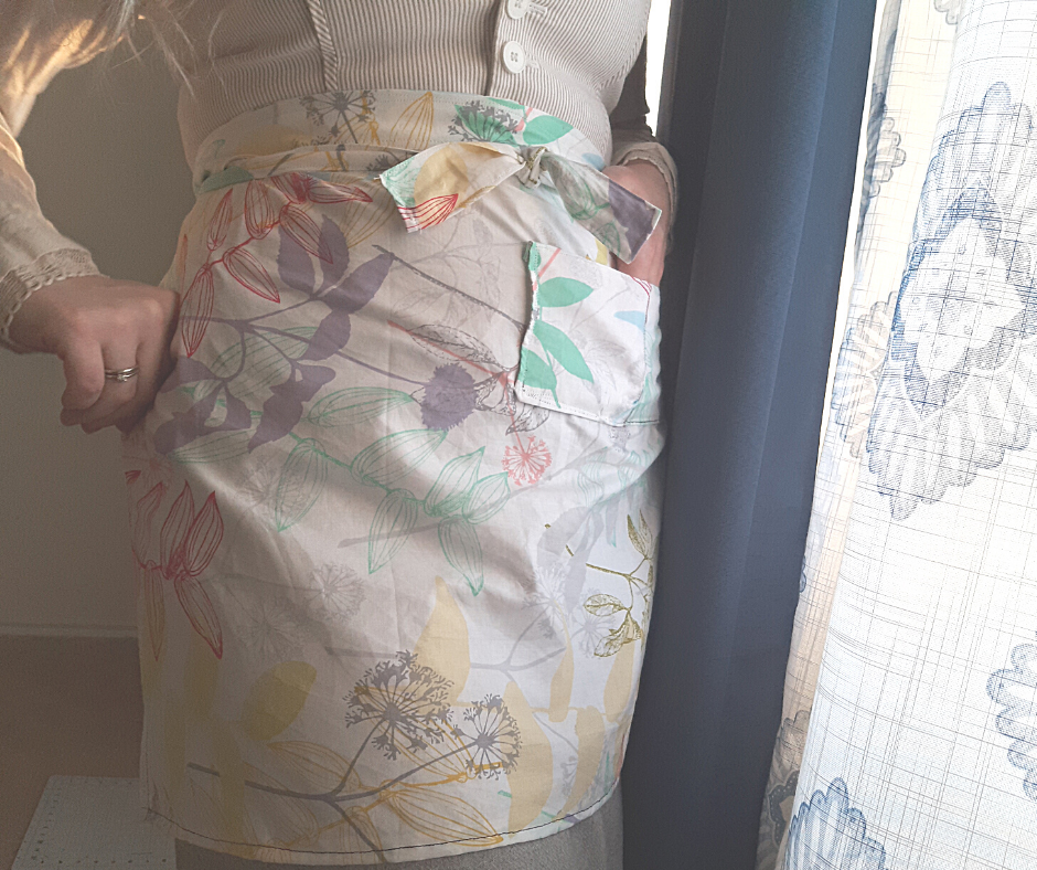 woman wearing a floral 1 hour apron with a pocket by curtains