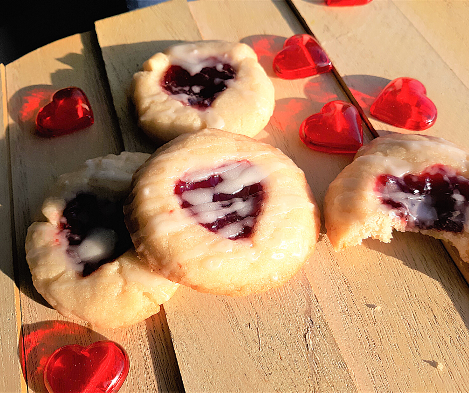 almond raspberry thumbprint cookies with read hearts, on wood, in the sun