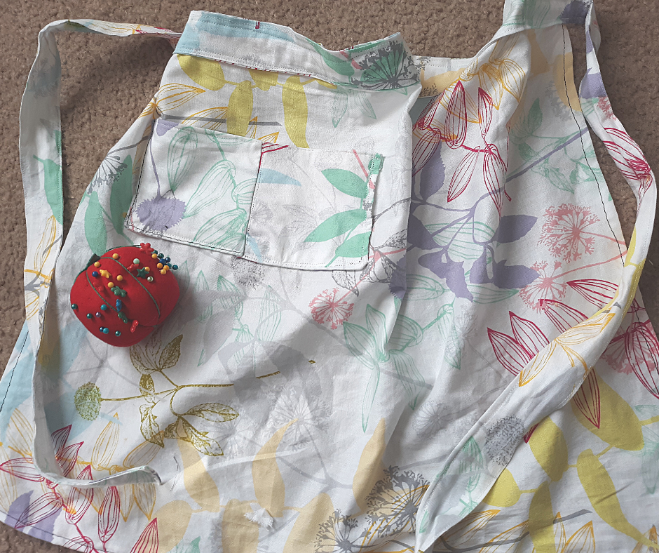 multicolored floral print 1-hour apron with a pocket, with a red tomato pin cushion on brown carpet