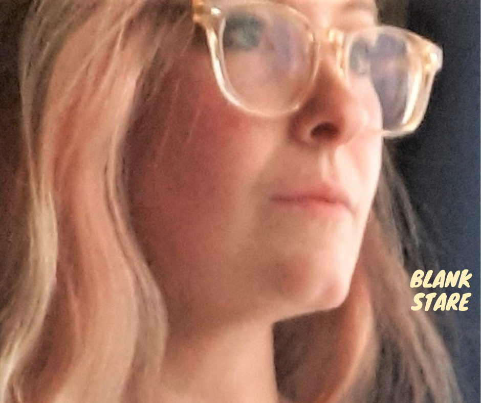 woman with blonde hair and gold glasses staring