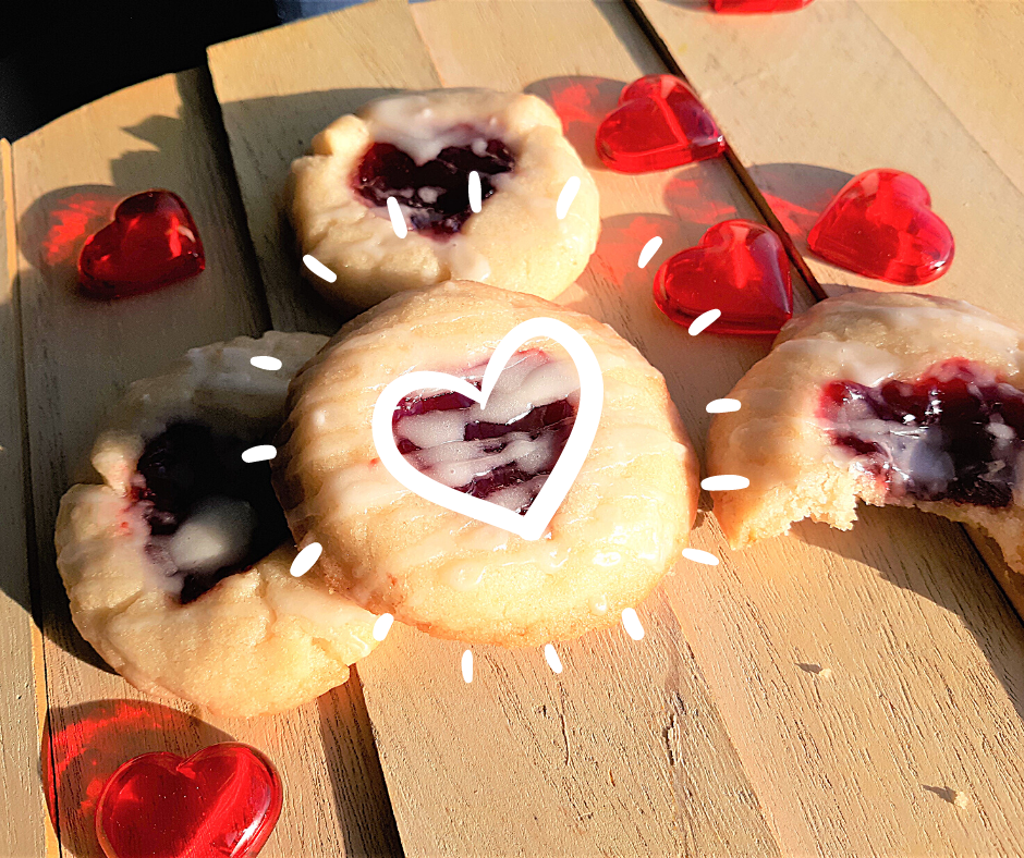 almond raspberry thumbprint cookies on wood in the sun with red heart shapes