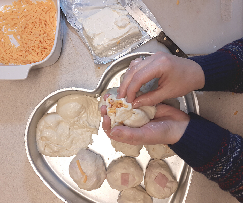 hands closing a dough ball full of ham and cheese over a pan with stuffed rolls and cream cheese and cheddar cheese off to the side