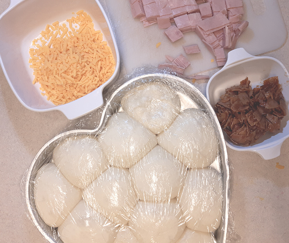 ingredients for ham and cheese stuffed rolls including risen dough balls, diced ham, cheddar cheese, BBQ ham