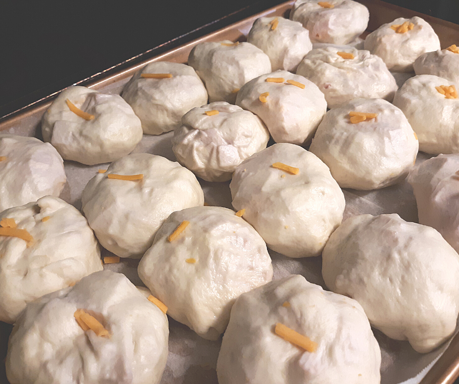 a pan of ham and cheese stuffed rolls, ready to be baked in the oven
