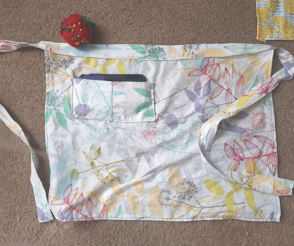 floral 1 hour apron with cell phone in pocket, red tomato pin cushion on brown carpet.