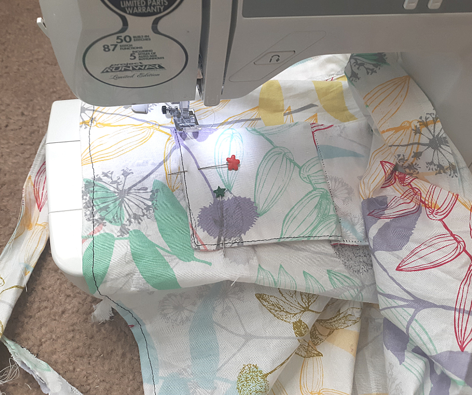 floral fabric pockets being sewn onto   in a white sewing machine with two sewing pins.