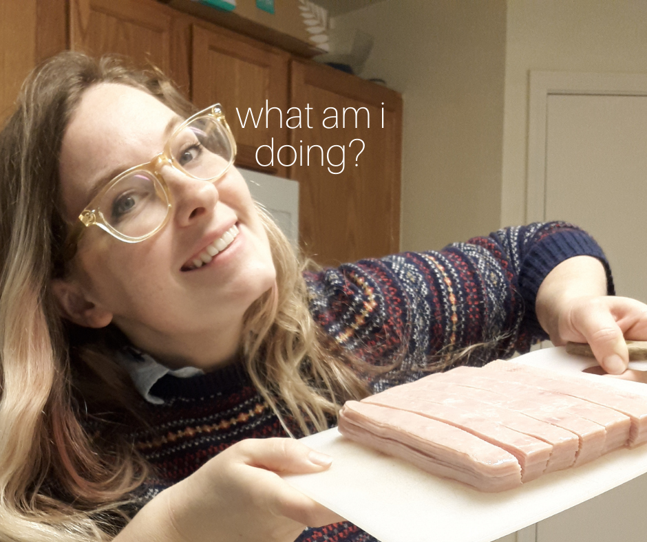 """smiling woman with glasses holding a cutting board with diced ham with the words """"what am i doing?"""""""