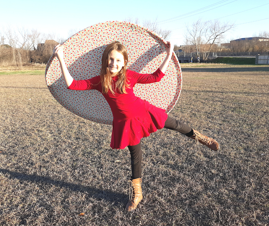 a girl holding a giant frisbee for a fun family activity
