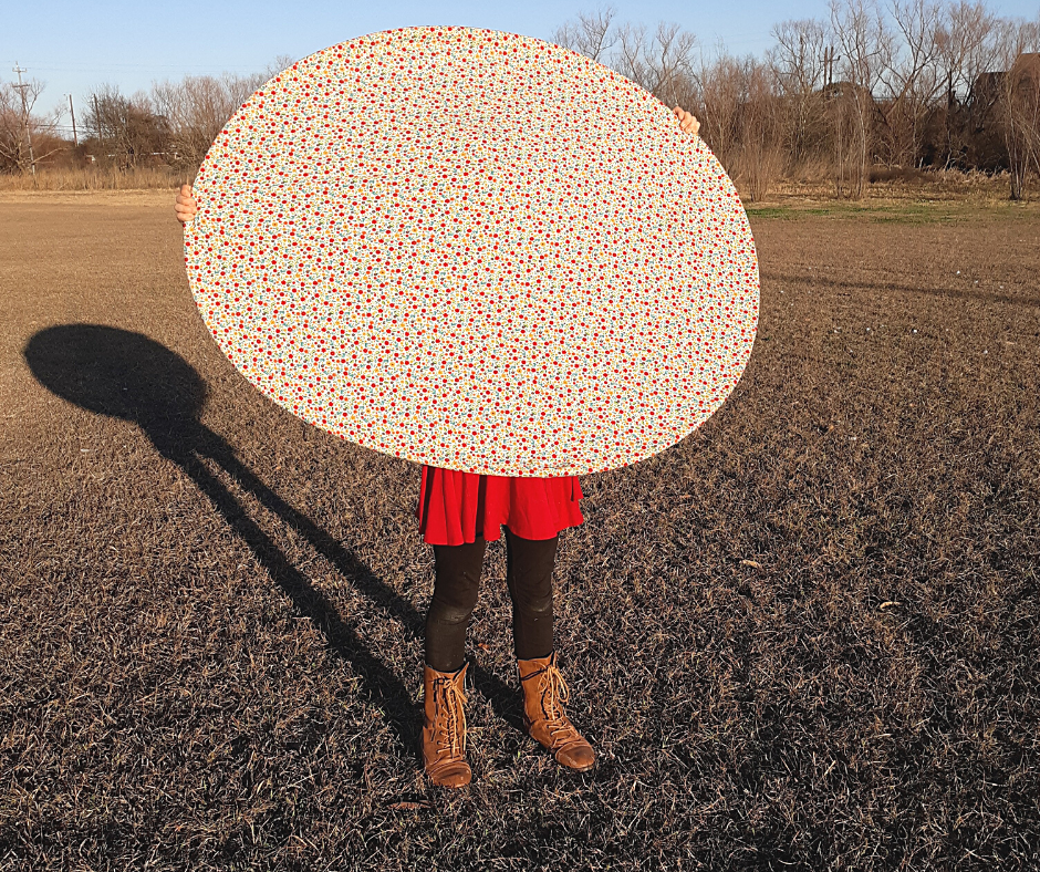 a girl holding a giant fabric frisbee in a field