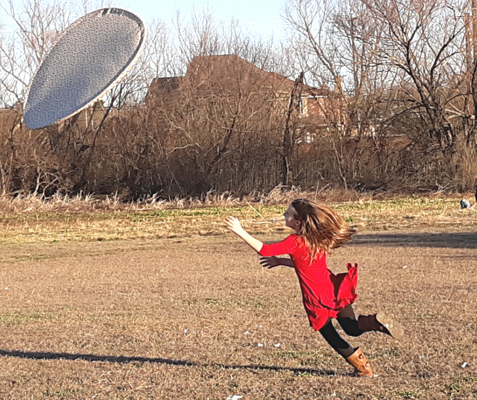 a girl leaping for a giant flying frisbee for a fun family activity