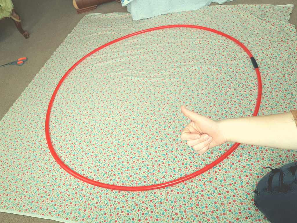 a red tube sitting on floral fabric with a thumbs up coming from the side