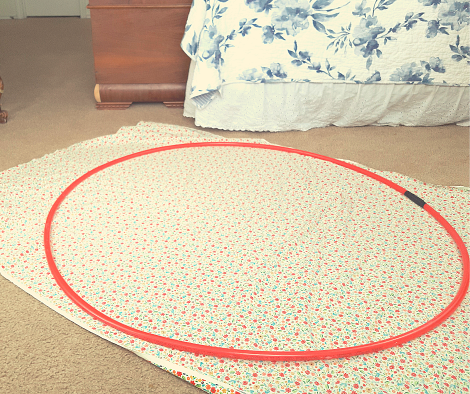 a read circle of tubing on floral fabric on the floor of a bedroom. materials for a fun family activity