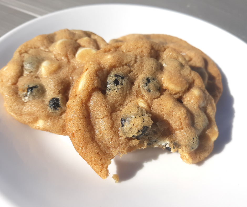 3 blueberry white chocolate cookies on a white plate with a bite out of one of them.