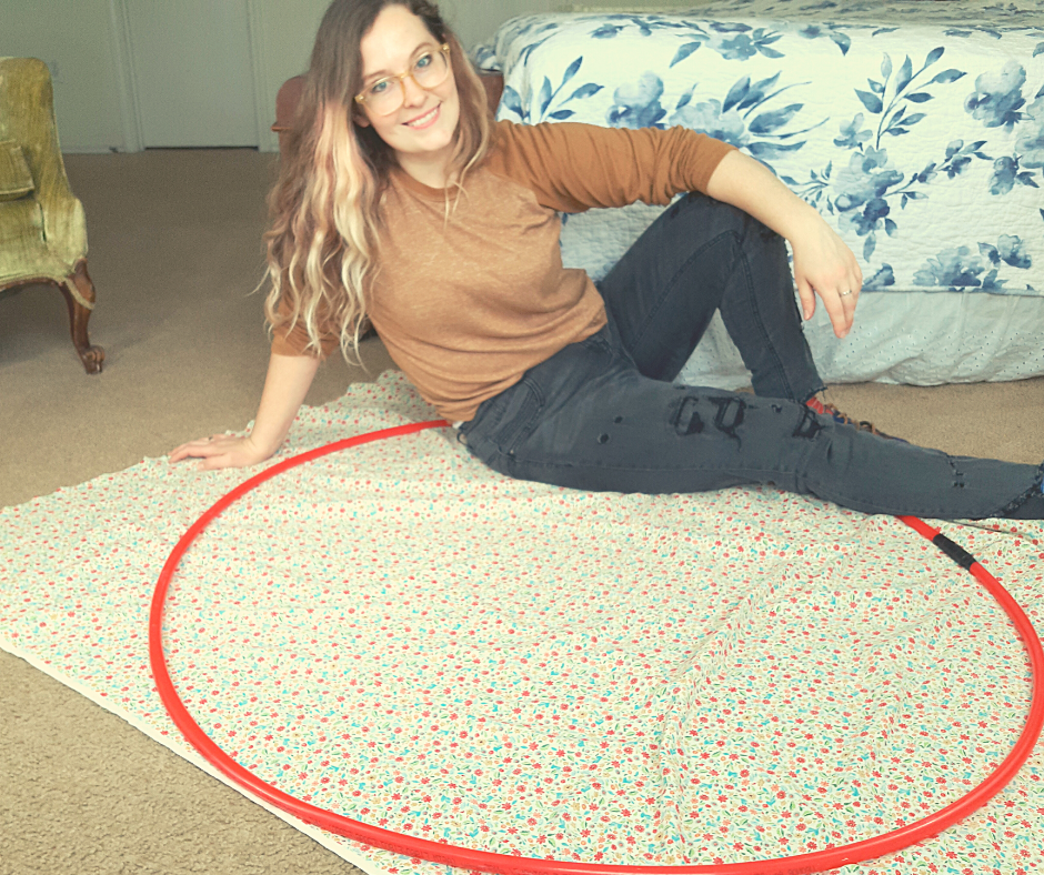 woman sitting on floral fabric and a red circle of tubing
