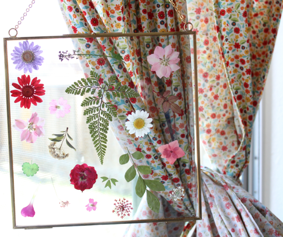 pressed flower frame in front of a window and flower curtain