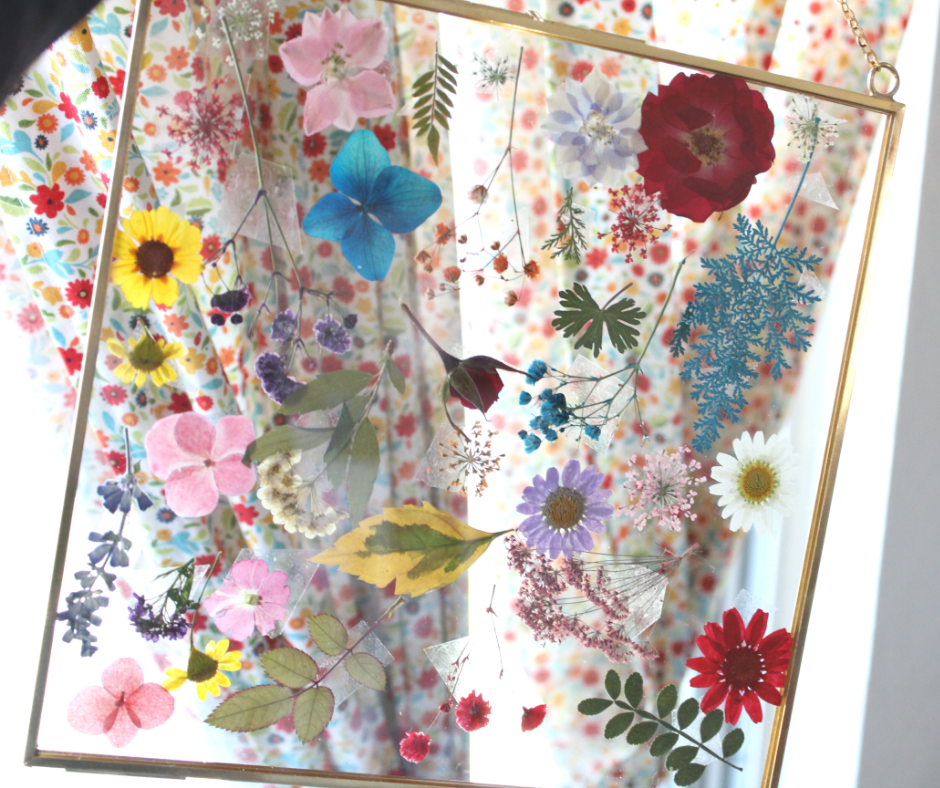 pressed flower frame in front on a curtain.