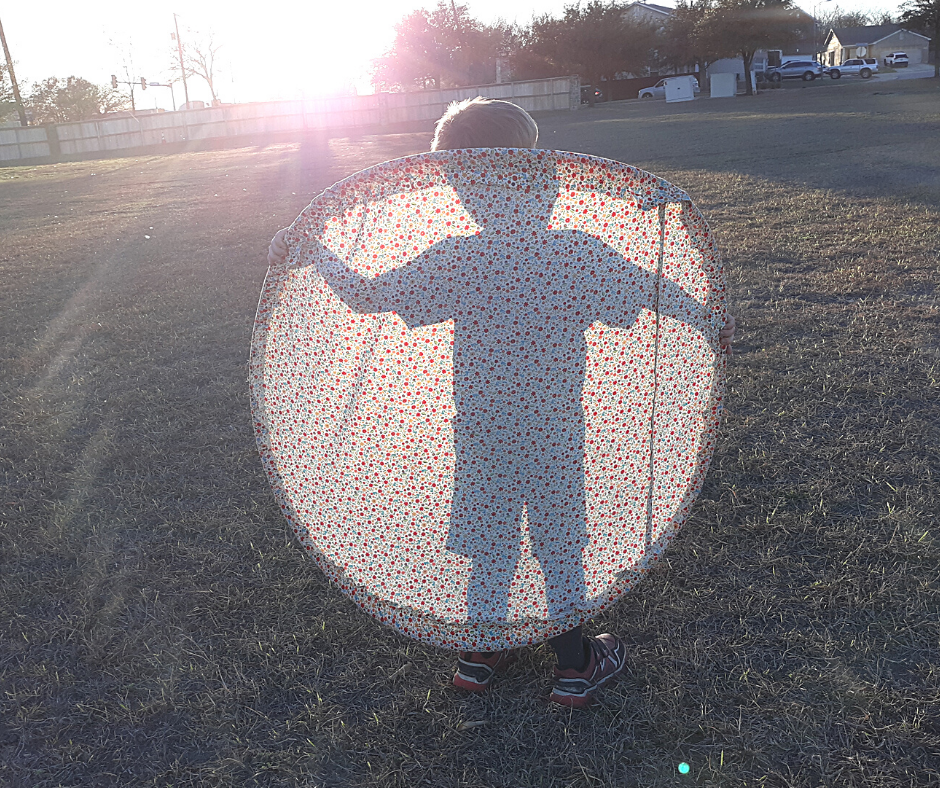 you can see the shadow of a boy holding a giant fabric frisbee in the sun