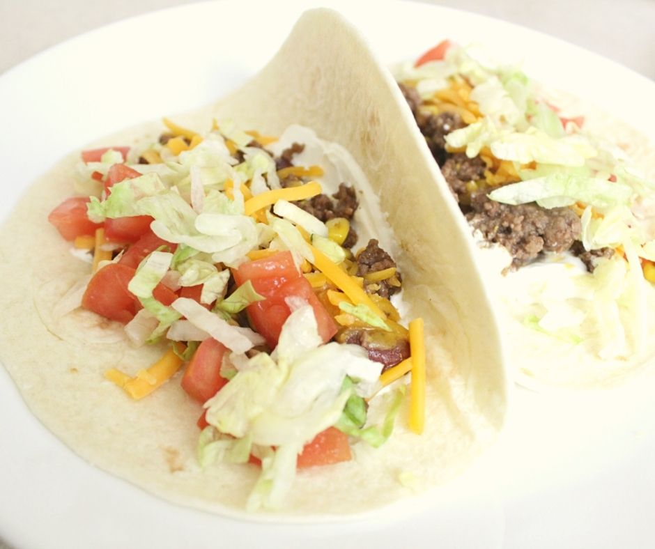 taco meat, shredded cheese, shredded lettuce, diced tomatoes, sour cream on a tortilla