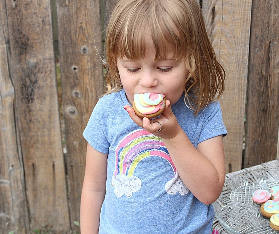a little girl biting a cheesecake cookie
