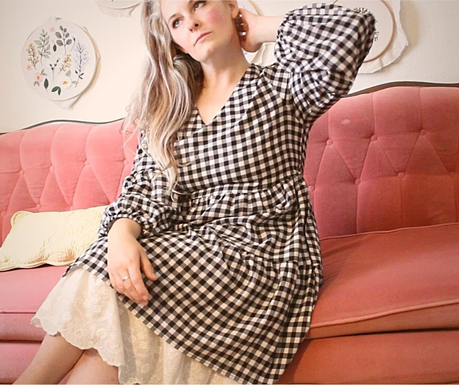 a girl in a checkered black and white dress with a white underskirt, sitting on a pink couch