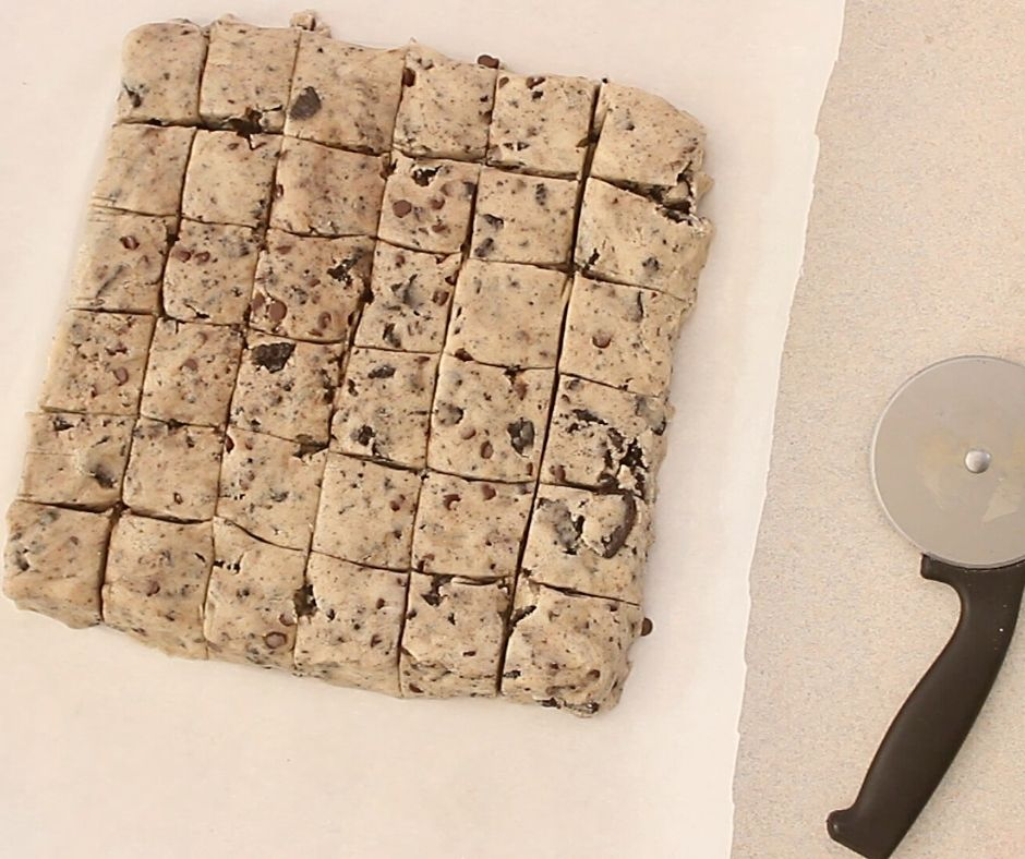 eggless cookie dough cut into 36 squares with a pizza cutter