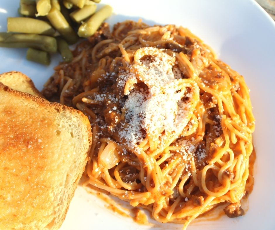 creamy spaghetti with bread and green beans on a white plate