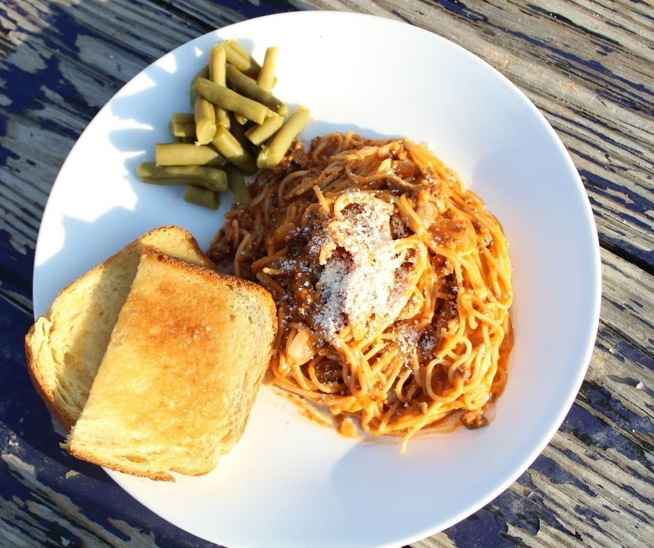 creamy spaghetti with garlic bread and green beans on a plate