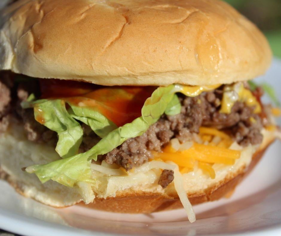 ground beef with cheese, lettuce, mayo, mustard, ketchup on an onion Hawaiian bread bun