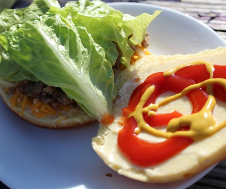 ground beef with hamburger toppings on a open face bun