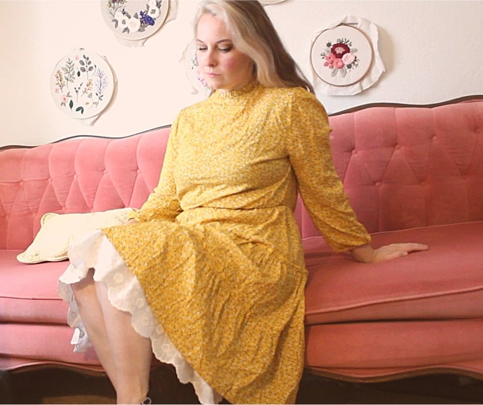 girl wearing a yellow dress with a white lace underskirt, sitting on a pink couch
