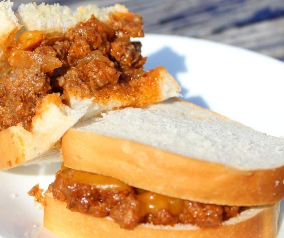 hot sandwiches with sloppy joe mix on a white plate
