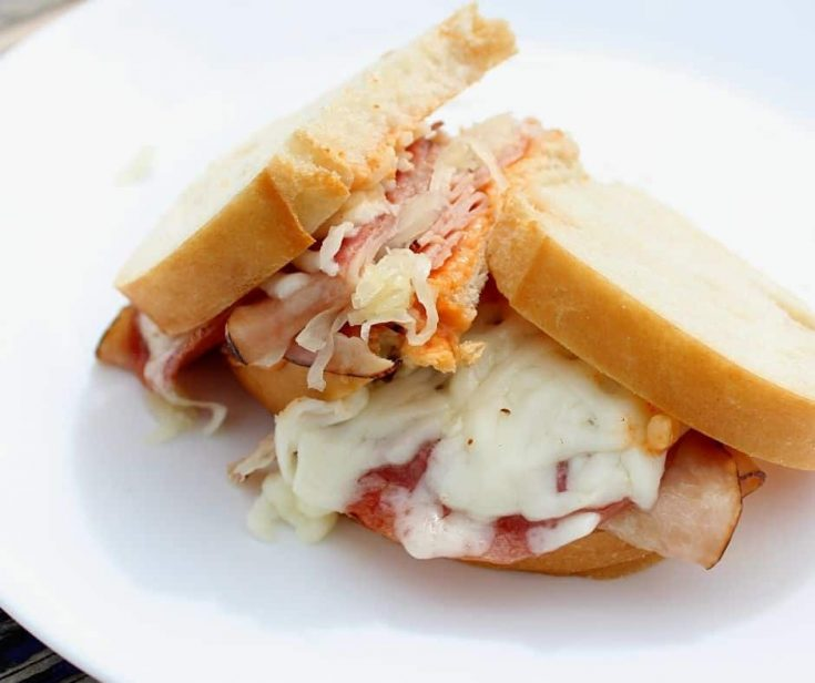 a hot sandwich made from meat and cheese on white bread on a plate