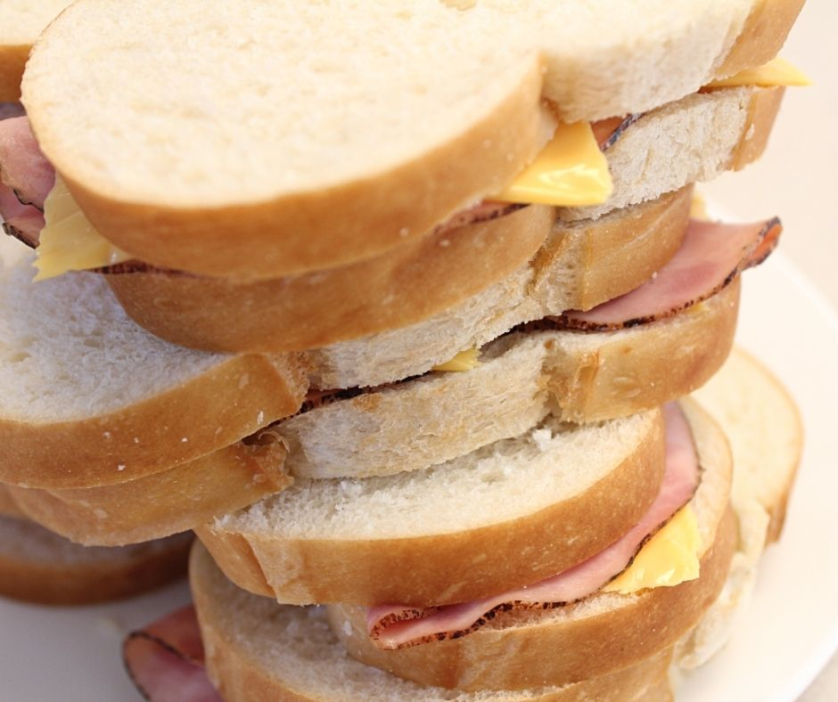 hot ham and cheese sandwiches stacked on a plate
