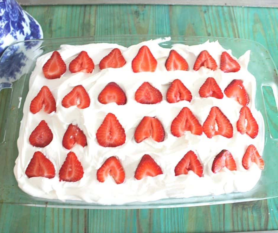 a poke cake with whipped cream and sliced strawberries on top on a green table