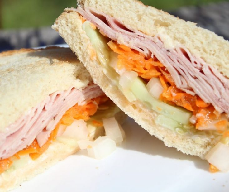 summer sandwich idea with mayo, ginger, cucumbers, onions, carrots, and ham on a white plate
