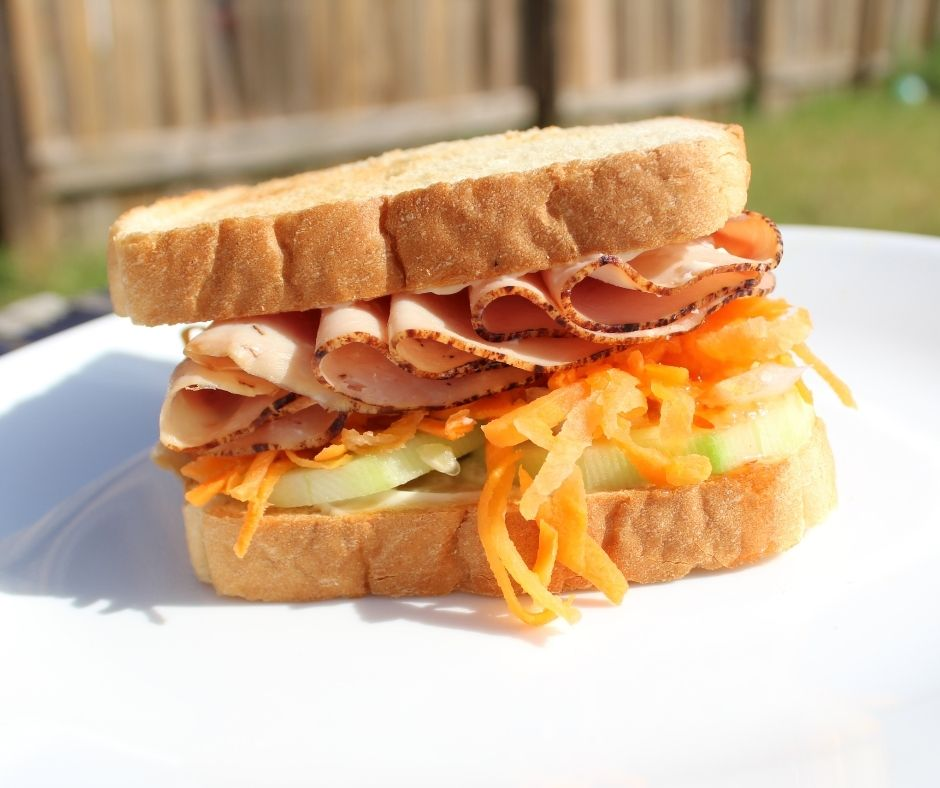 a sandwich idea that has carrots and onions in the sandwich on a white plate