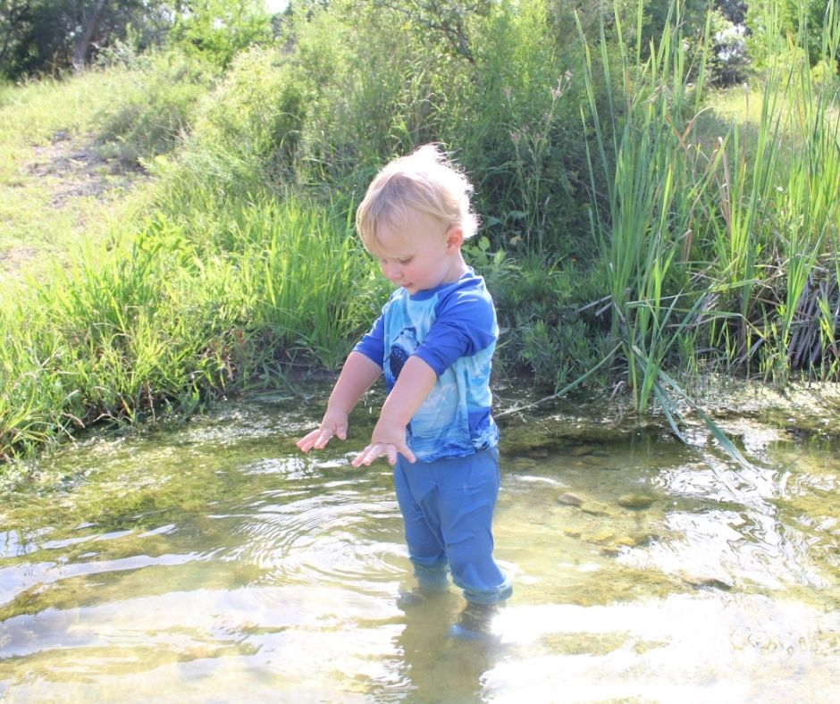 little boy playing in the pond