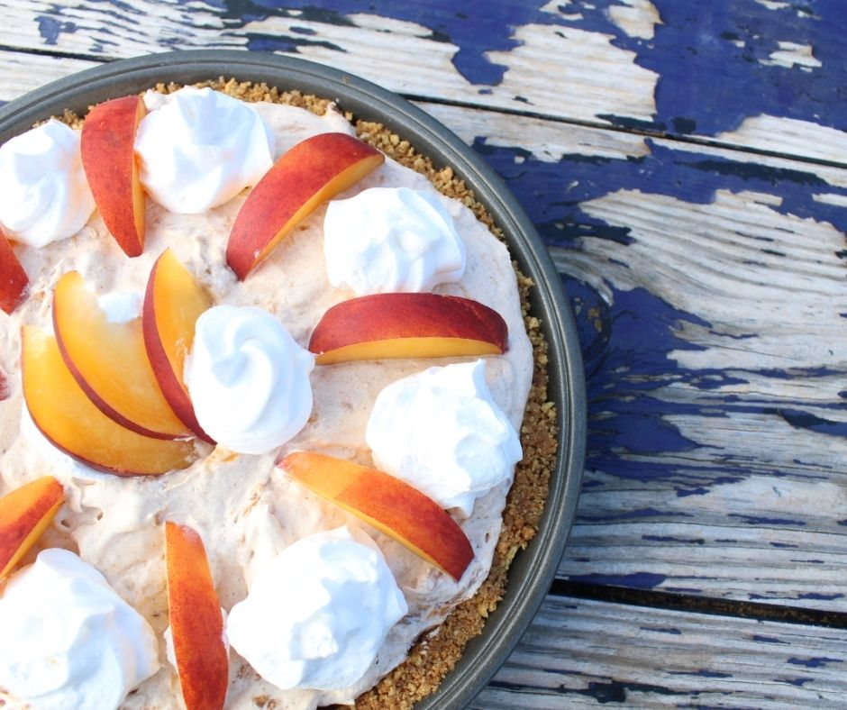 whipped peach pie with whipped cream and slices of peaches on top, on a wooden table with peeling blue paint